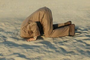 Picture of a man bowing in a Muslim posture of worship, but his head is buried in the sand.