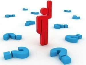 Image of a man standing in the middle of question marks. He is holding up his hand to answer a question.