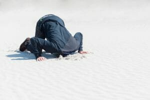 Photo of a man with his head buried in the sand in the position of Islamic worship.