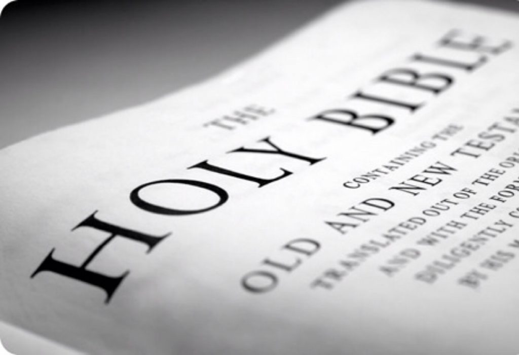 Image de la Bible ouverte. On peut y lire, « The Holy Bible. »