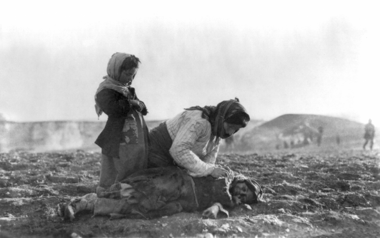 Image of an Armenian woman kneeling beside dead child in a field near Aleppo
